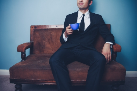 Young businessman sitting on vintage sofa drinking coffee Stock Photo - 22141145
