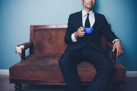 Young businessman sitting on vintage sofa drinking coffee Stock Photo - 22141146