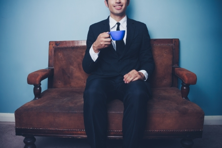 Young businessman sitting on vintage sofa drinking coffee photo