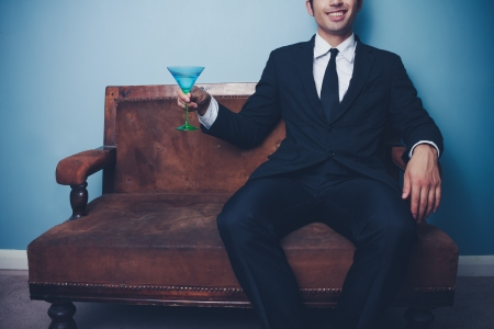 jetset: Young businessman on old vintage sofa toasting with a cocktail  Stock Photo