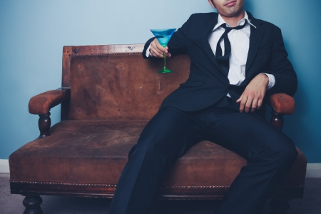 drunken: Businessman is relaxing on an old sofa with a glass of martini