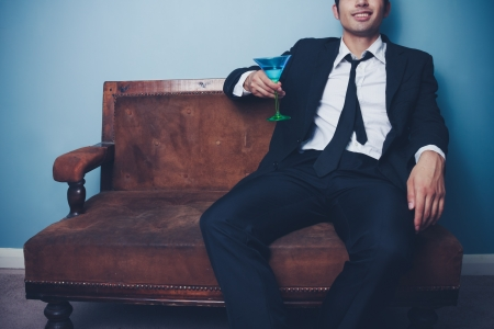 jetset: Businessman is relaxing on an old sofa with a glass of martini