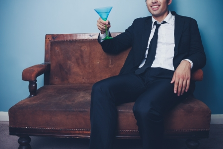 Businessman is relaxing on an old sofa with a glass of martini Stock Photo - 22159502