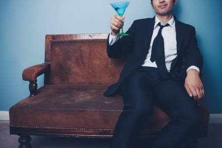 Businessman is relaxing on an old sofa with a glass of martini photo