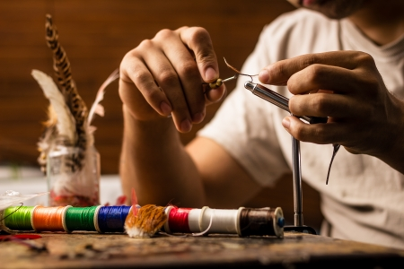 craftsperson: Young man tying flies for fly fishing