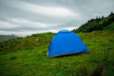 camping pitch: Blue tent pitched on a hillside in the wilderness