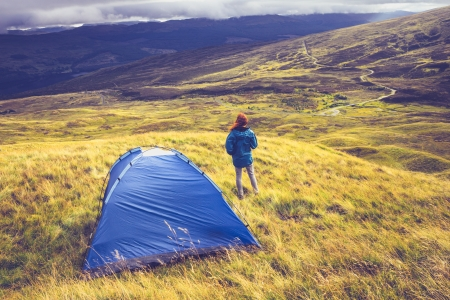 recreational area: Woman is camping on top of a mountain in the wilderness Stock Photo