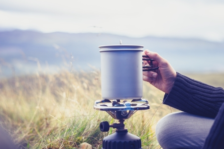 survive: Young woman is camping and cooking on a portable stove