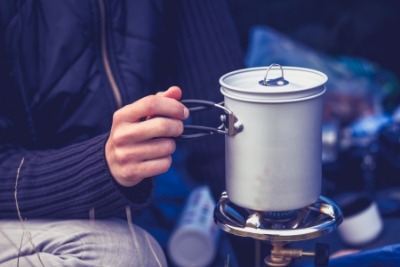 boiling: Young woman is camping and cooking on a portable stove