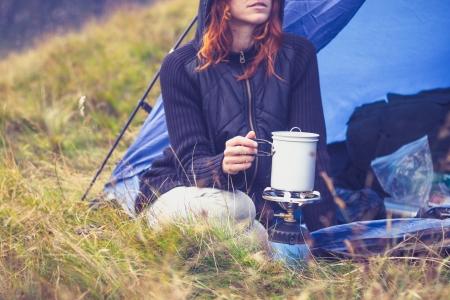 La mujer joven está acampando y cocinar en una estufa portátil