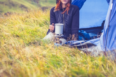 Young woman is camping and cooking on a portable stove photo