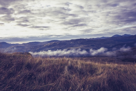 Mist and clouds arolling across spectacular mountain landscape photo