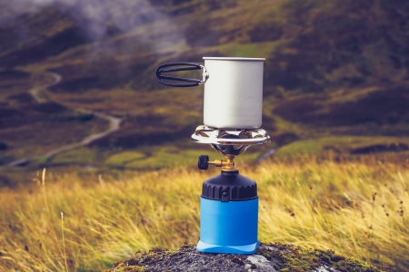 CAmping stove with pot of boiling water in the mountains photo