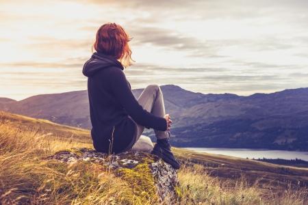 La jeune femme est assis sur le dessus de la montagne en admirant le coucher du soleil