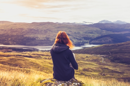 Young woman is sitting on top of mountain admiring the sunset Stock Photo