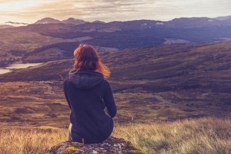 夕日を眺め山の頂上に座っている若い女性