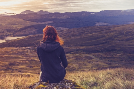 quiet adult: Young woman is sitting on top of mountain admiring the sunset Stock Photo