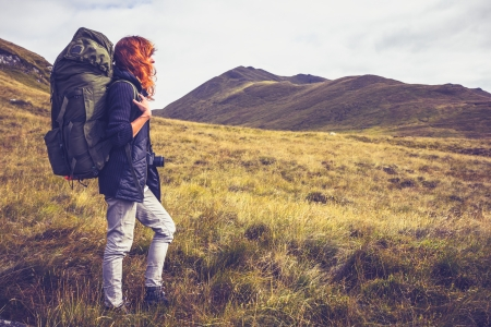 Young woman is trekking through the mountains with backpack photo