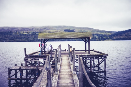Old pier at lake on gloomy day Stock Photo - 22259913