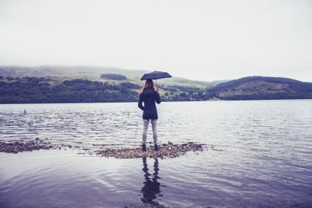 Woman standing in lake holding umbrella Stock Photo - 22259919
