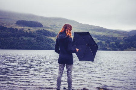 Woman standing in lake holding umbrella photo
