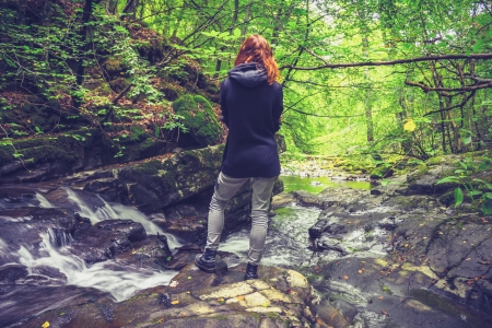 Young woman admiring flowing water in forest photo