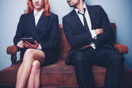 sloppy: Businesswoman reading on tablet with sloppy male coworker spying on her Stock Photo