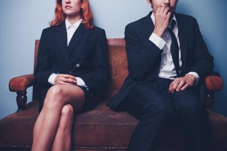 神経質なビジネスマンの隣に座っている自信を持って女性実業家 写真素材