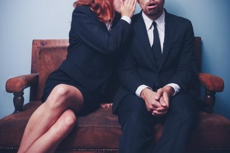 Joven mujer de negocios está chismeando a compañero de trabajo masculino