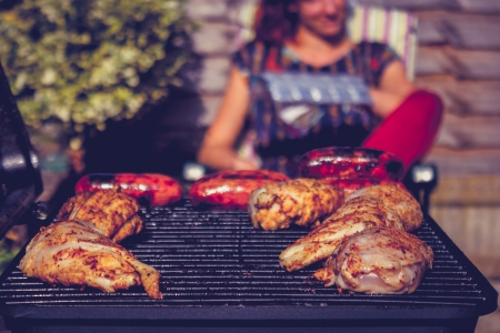preperation: Chicken grilling on barbecue with woman