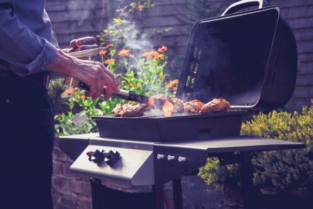 Man is cooking outdoors at barbecue photo
