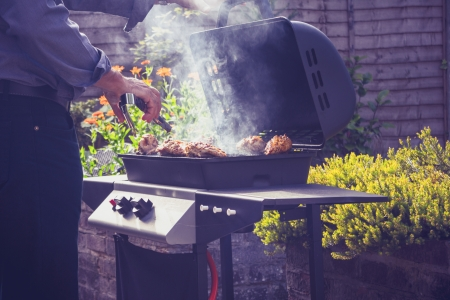 charcoal grill: Man is cooking outdoors at barbecue