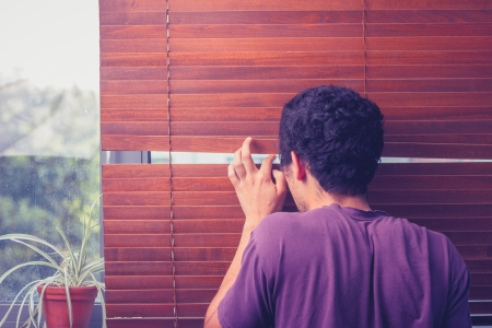 Young man peeping out through his venetian blinds
