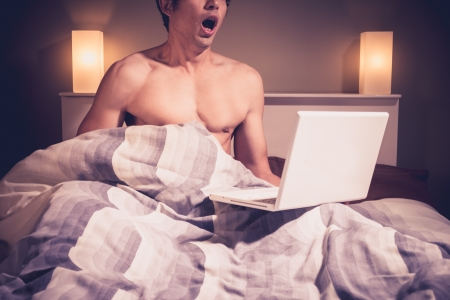 Young naked man in bed is watching pornography on laptop