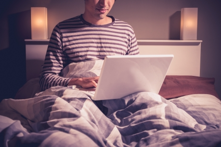 Young man in bed using laptop computer