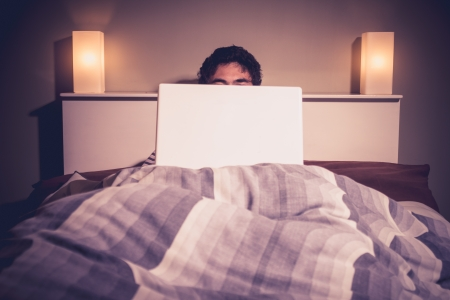 Young man in bed is hiding behind his laptop photo