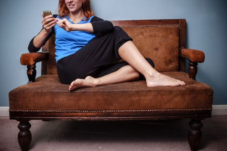 Happy young woman sitting on sofa and using her phone photo