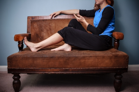 Young woman sitting on sofa and using her phone photo