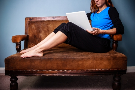 Young woman is sitting on sofa and watching something on her laptop photo