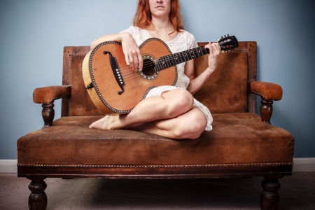 Young woman in white dress on sofa is playing guitar photo