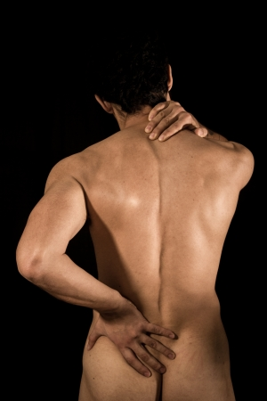 Young naked man with pain in his lower back and neck photo