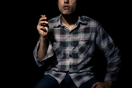 Man is sitting and smoking in the dark photo