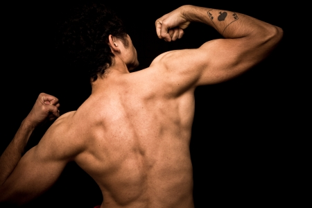 dorsi: Athletic and muscular young man posing on black background Stock Photo
