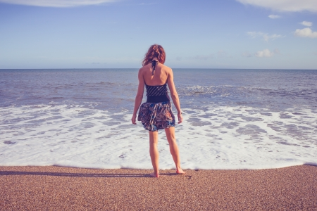 Young woman standing in the surf on the beach looking at the ocean photo