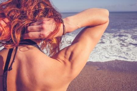 undoing: Young woman undoing her bikini on the beach