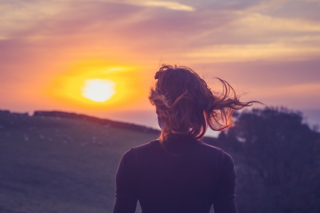 Young woman admiring the sunset over a field photo