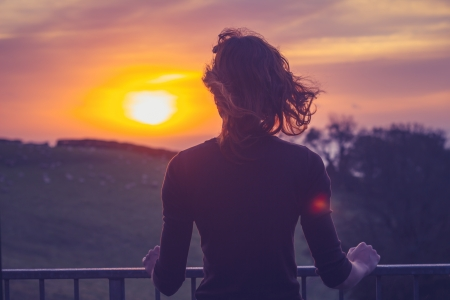 back views: Young woman admiring the sunset from her balcony Stock Photo