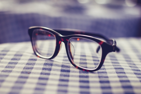 eyeglasses: Pair of glasses on a checkered tablecloth