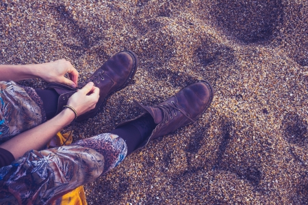 Woman on the beach is tying the laces of her hiking boots photo