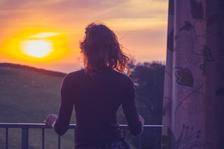 Young woman admiring the sunset from her apartment s balcony